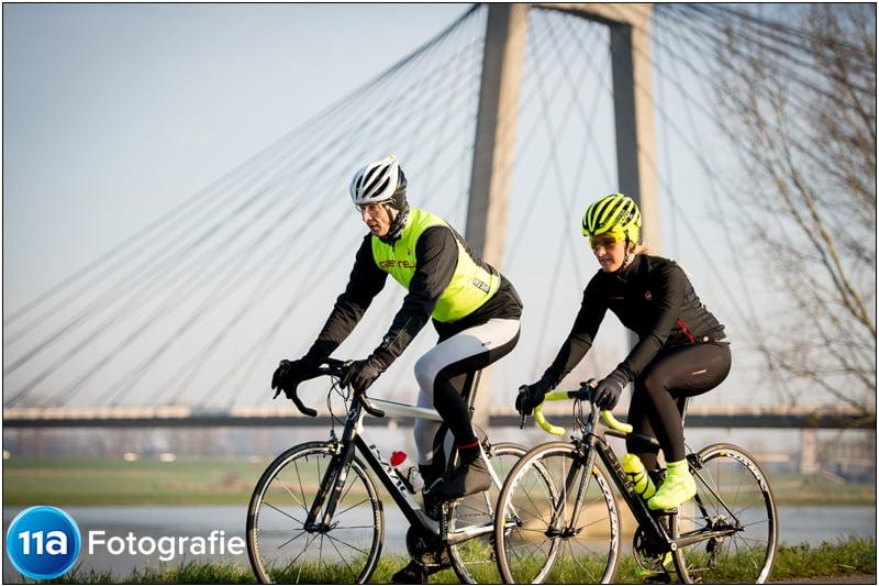 Wielerfoto met de brug bij Heusden als achtergrond