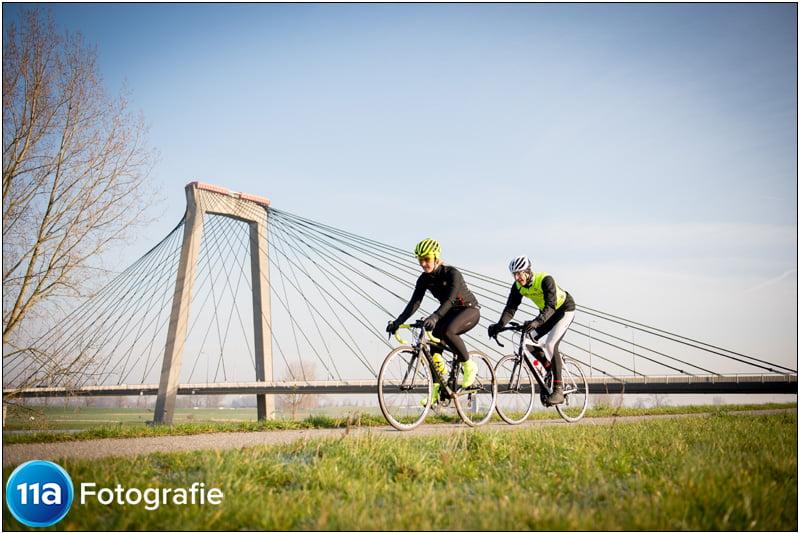 Wielerfoto van 2 fietsers met de brug van Heusden op de achtergrond