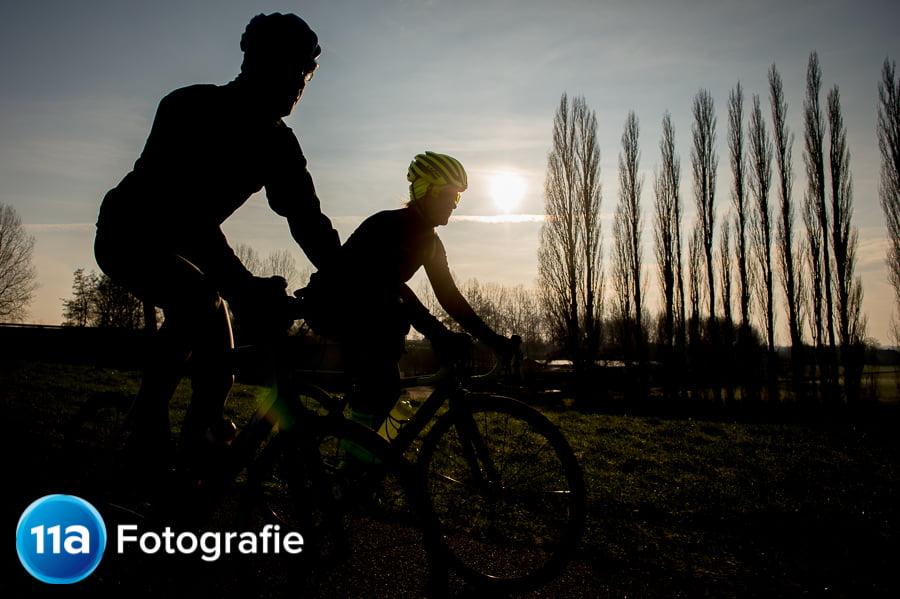 Wielerfoto met een prachtige zonsopkomst en de fietsers in silhouette